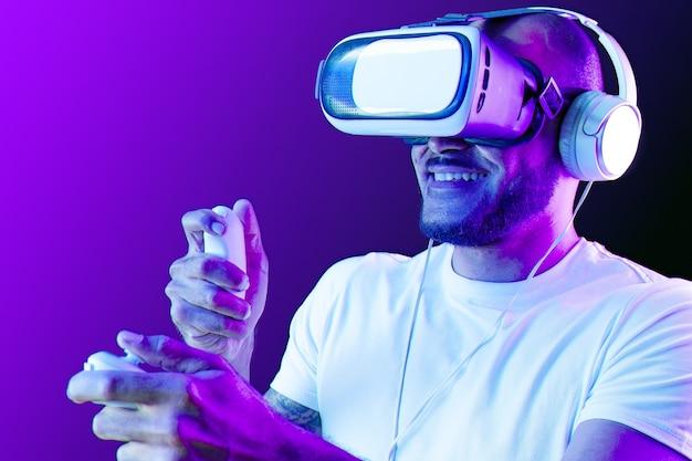 Uomo afroamericano che indossa occhiali vr in luce al neon su sfondo viola da vicino