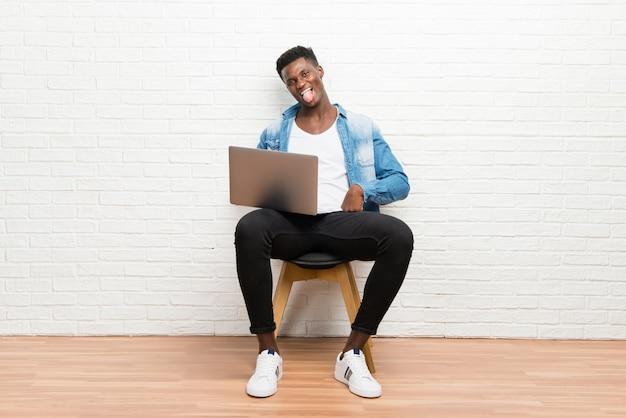Uomo afroamericano che lavora con il suo computer portatile che mostra lingua alla macchina fotografica che ha sguardo divertente