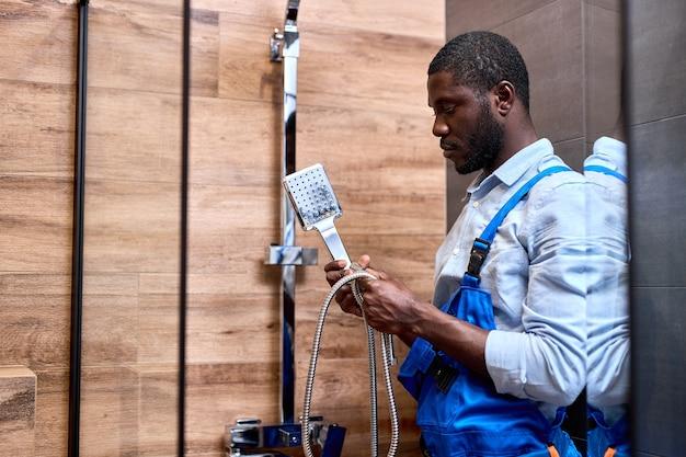 Riparatore afroamericano tuttofare in tuta blu che tiene la maniglia della doccia in mano mentre ripara l'installazione, nel bagno del cliente a casa. fiducioso ragazzo serio impegnato in lavori idraulici