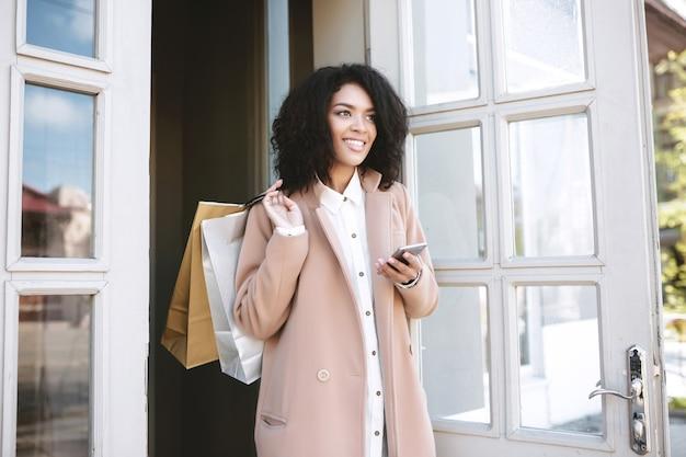 Ragazza sorridente afro-americana in piedi con i pacchetti e il telefono nelle sue mani