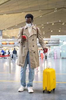 Uomo viaggiatore afroamericano che indossa la maschera durante la pandemia di coronavirus in piedi al terminal dell'aeroporto