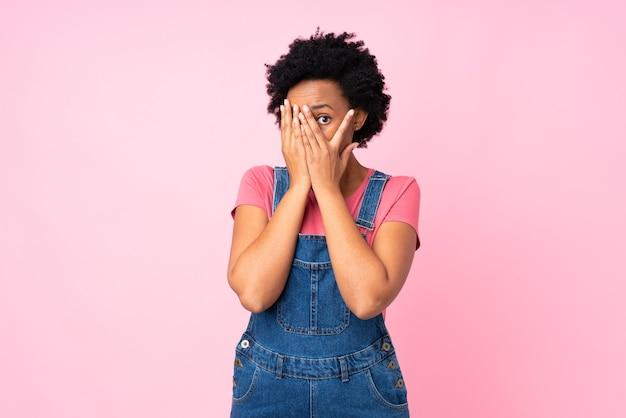 Donna afro americana che nasconde il viso con le mani isolate su sfondo rosa