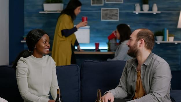Donna afroamericana che si rilassa sul divano mentre dà il cinque con un amico uomo