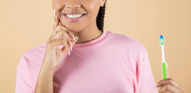 Sorriso di donna afroamericana con spazzolino da denti, sfondo beige