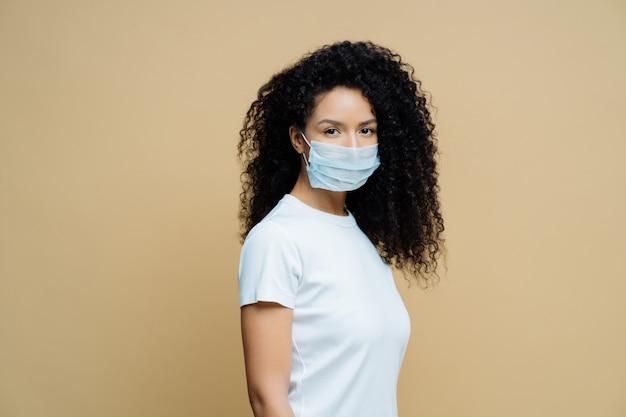 La donna afroamericana indossa una maschera protettiva, protegge dalla diffusione della coronavirus