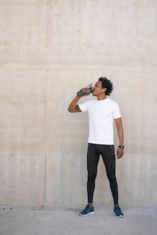 Acqua potabile dell'uomo atletico afro e rilassarsi dopo l'allenamento all'aperto. sport e concetto di stile di vita sano.