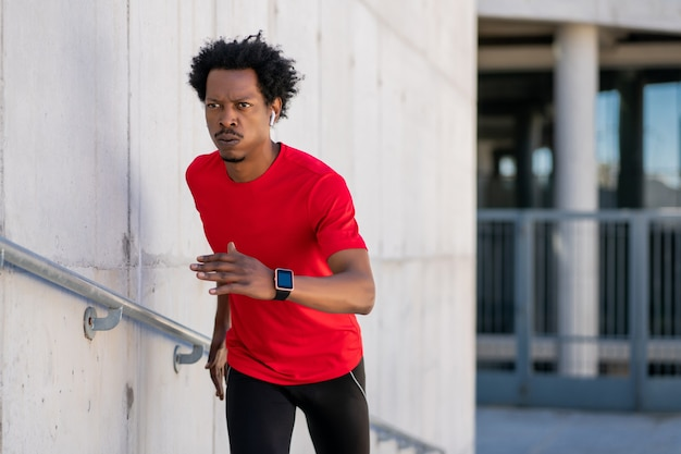 Uomo atletico afro che corre e fa esercizio all'aperto per strada. sport e concetto di stile di vita sano.