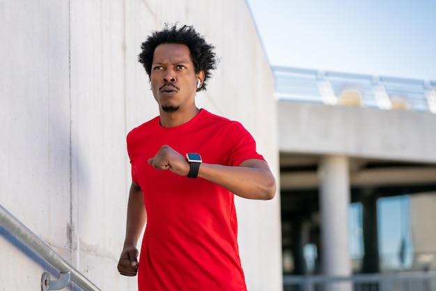Uomo atletico afro correre e fare esercizio all'aperto sulla strada
