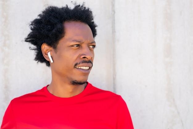 Uomo atletico afro in piedi all'aperto sulla strada