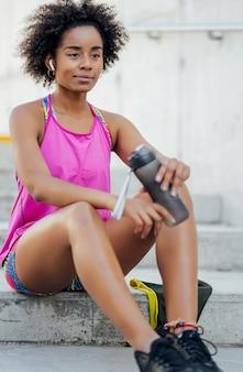 Afro donna atletica acqua potabile e rilassarsi dopo l'allenamento mentre è seduto sulle scale all'aperto.