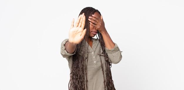 Donna adulta nera afro che copre il viso con la mano e mette l'altra mano davanti per fermare la fotocamera, rifiutando foto o immagini