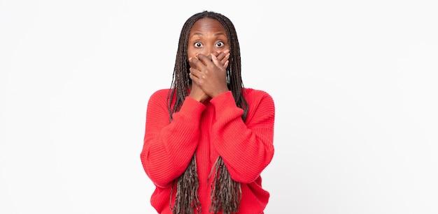 Donna adulta nera afro che copre la bocca con le mani con un'espressione scioccata e sorpresa, mantenendo un segreto o dicendo oops