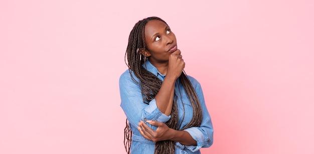 Donna adulta afro nera che si sente premurosa, chiedendosi o immaginando idee, sognando ad occhi aperti e alzando lo sguardo per copiare lo spazio
