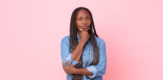 Donna adulta nera afro che sembra seria, premurosa e diffidente, con un braccio incrociato e la mano sul mento, opzioni di ponderazione