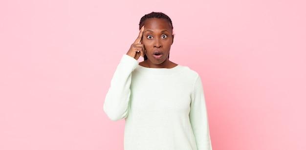 Donna adulta afro nera che sembra sorpresa, a bocca aperta, scioccata, realizzando un nuovo pensiero, idea o concetto