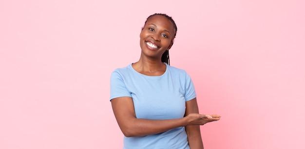 Donna adulta nera afro che sorride allegramente, si sente felice e mostra un concetto nello spazio della copia con il palmo della mano