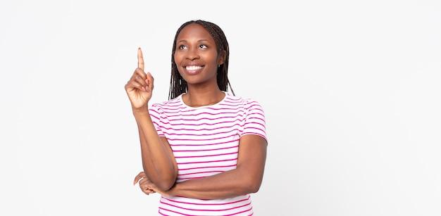 Donna adulta afro nera che sorride felicemente e guarda di traverso, chiedendosi, pensando o avendo un'idea