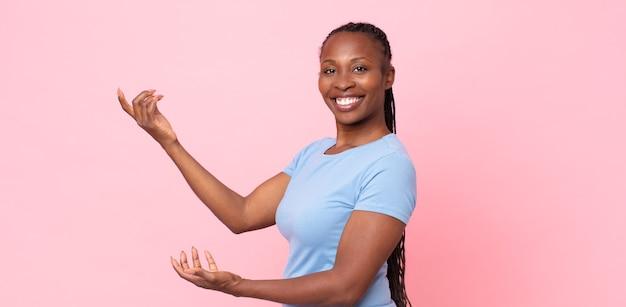 Donna adulta afro nera che sorride con orgoglio e fiducia, sentendosi felice e soddisfatta e mostrando un concetto sullo spazio della copia