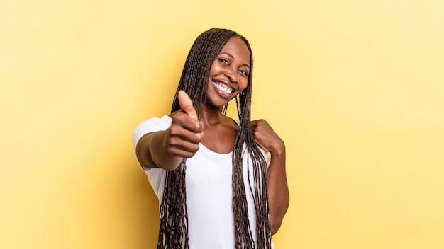 Bella donna afro nera che si sente orgogliosa, spensierata, sicura di sé e felice, sorridendo positivamente con il pollice in alto