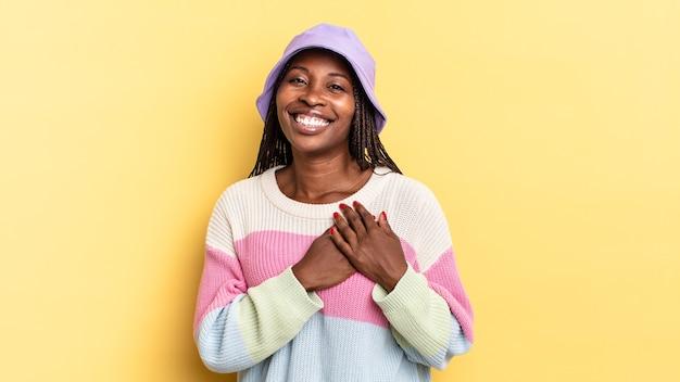 Bella donna afro nera che si sente romantica, felice e innamorata, sorride allegramente e si tiene per mano vicino al cuore