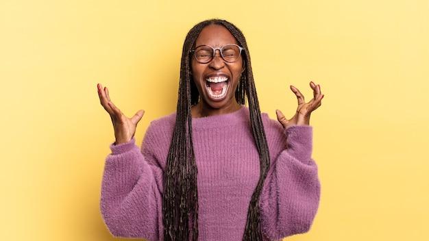 Una bella donna afro nera che urla furiosamente, si sente stressata e infastidita con le mani in aria dicendo perché me