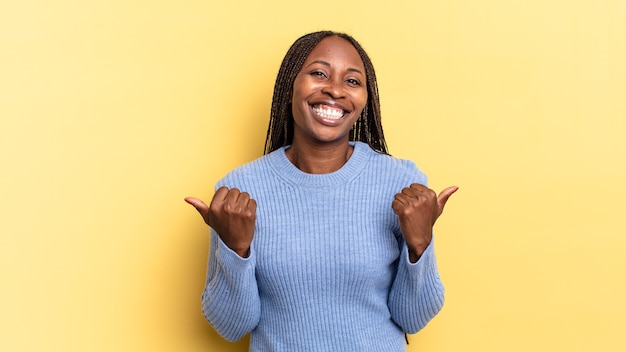 Bella donna afro nera che sorride gioiosamente e sembra felice, si sente spensierata e positiva con entrambi i pollici in su