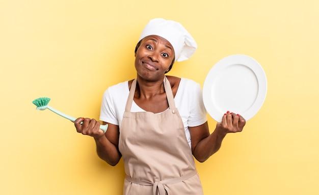 Donna graziosa afro nera che lava i piatti concept