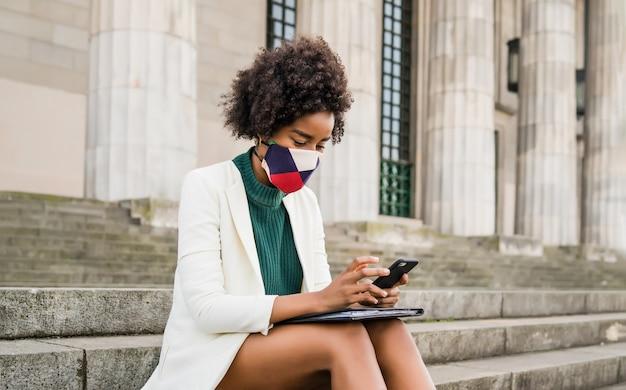 Donna d'affari afro indossando maschera protettiva e utilizzando il suo telefono cellulare