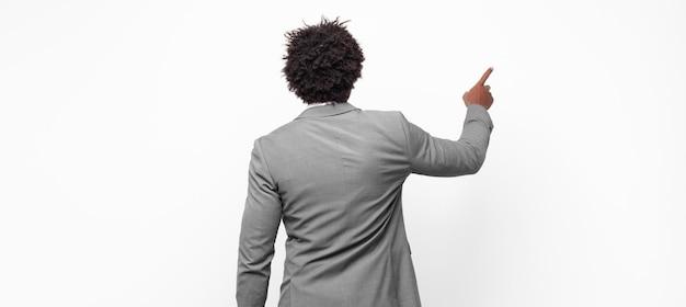 Uomo d'affari afro in piedi e punta a un oggetto sullo spazio della copia, vista posteriore