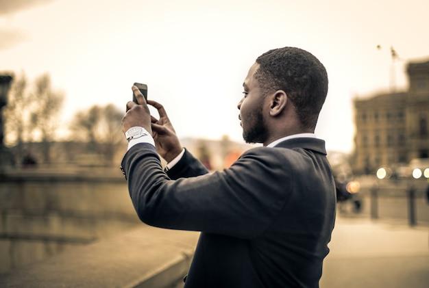 Uomo d'affari afro che prende una foto