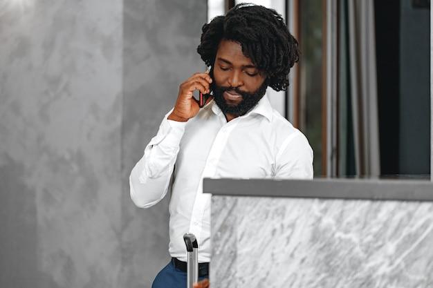 Uomo d'affari afro in camicia bianca, parlando al telefono si chiuda