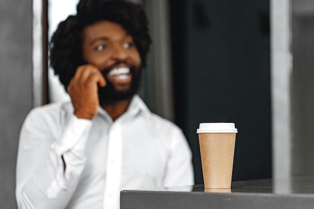 Uomo d'affari afro in camicia bianca, parlando al telefono