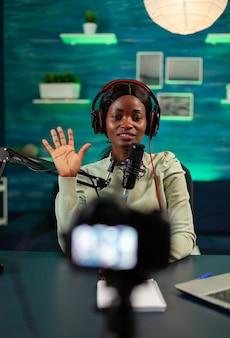 Creatore di contenuti afro saluta gli ascoltatori che indossano le cuffie. host di trasmissione internet di produzione in onda in streaming di contenuti live, registrazione di social media digitali