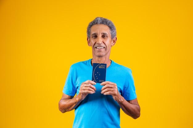 Uomo anziano afro che tiene in mano il passaporto brasiliano