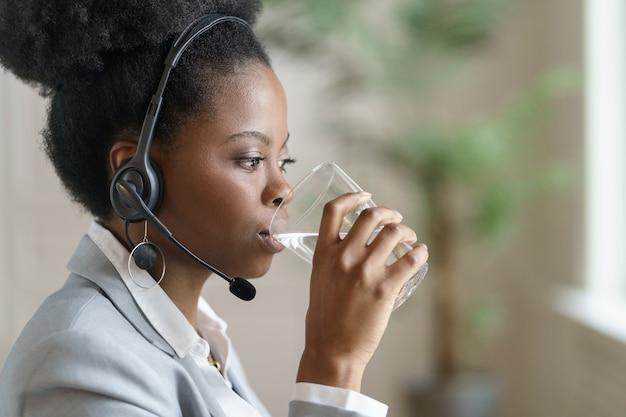 Donna dipendente afro in giacca sportiva con le cuffie guardando l'acqua potabile dello schermo del computer da un bicchiere