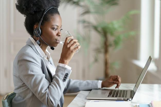Donna dipendente afro guardando lo schermo del laptop, lavorando in ufficio a casa, acqua potabile da un bicchiere.