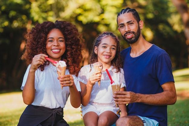 Famiglia afro nel parco a mangiare il gelato