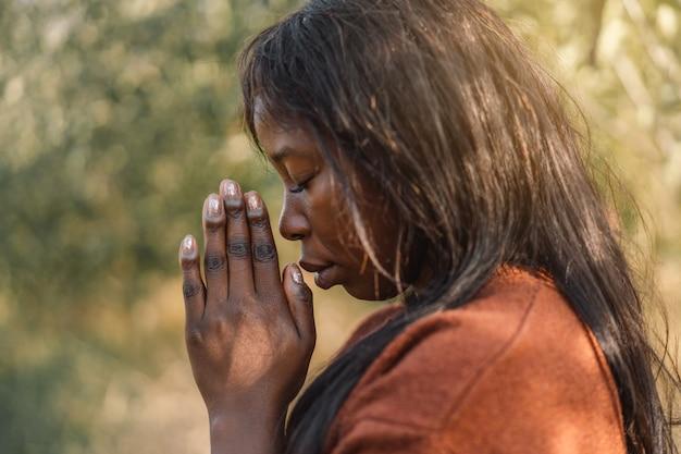 Ragazza afro con gli occhi chiusi, pregando all'aperto