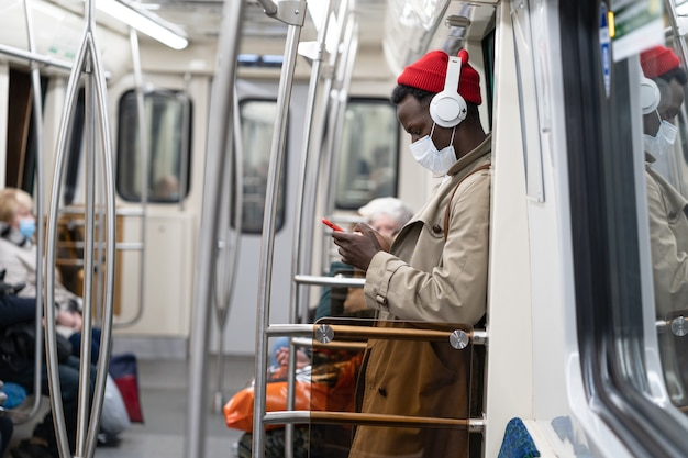 Uomo passeggero afro in treno della metropolitana, indossa una maschera per proteggersi da covid, usa il telefono, ascolta musica