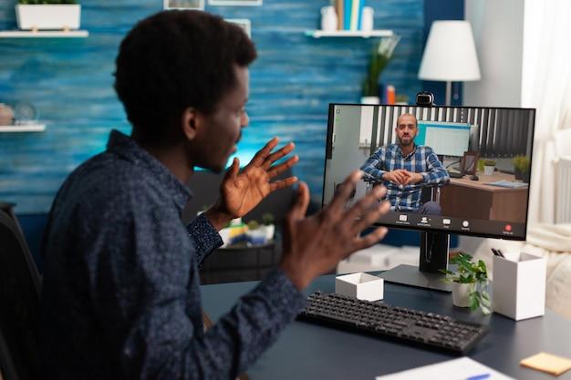Studente afro che discute la strategia aziendale con un insegnante universitario remoto sulla piattaforma di e-learning della scuola durante la conferenza videochiamata online. telelavoro in videoconferenza chiamata su computer