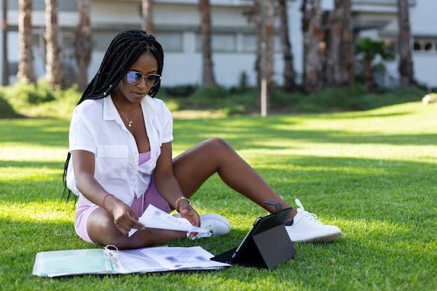 Studentessa afro seduta nel parco a guardare le note.