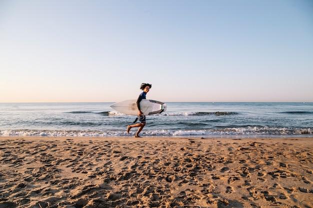 Afro surfista che corre con tavole da surf lungo la riva
