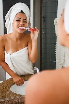 Donna afro che si lava i denti in bagno