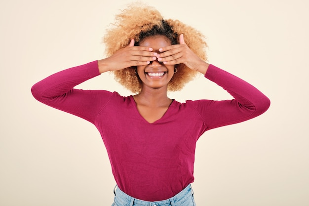 Donna afro che si copre gli occhi con le mani e sorride mentre si trova su uno sfondo isolato.