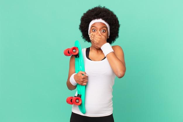 Donna afro che copre la bocca con le mani con un'espressione scioccata e sorpresa, mantenendo un segreto o dicendo oops. concetto di skateboard