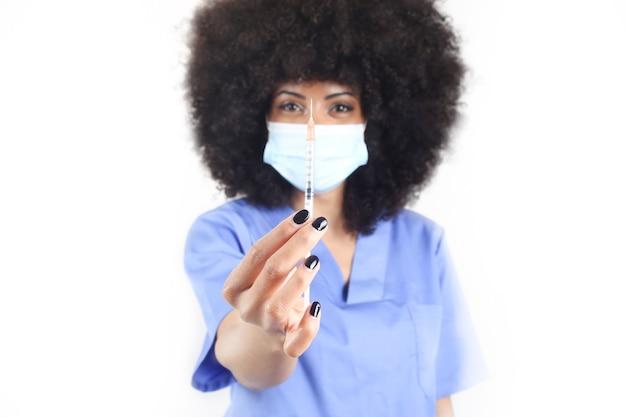Medico donna afro con maschera medica che mostra siringa, concetto di vaccino covid-19 Foto Premium