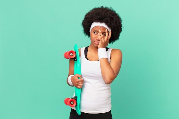 La donna afro si sente annoiata, frustrata e assonnata dopo un compito noioso, noioso e noioso, tenendo il viso con la mano. concetto di skateboard