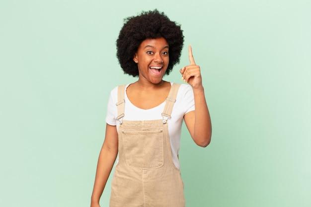 Donna afro che si sente un genio felice ed eccitato dopo aver realizzato un'idea, alzando allegramente il dito, eureka! concetto di chef