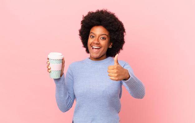 Donna afro che si sente orgogliosa, spensierata, sicura di sé e felice, sorridendo positivamente con il pollice in alto. concetto di caffè