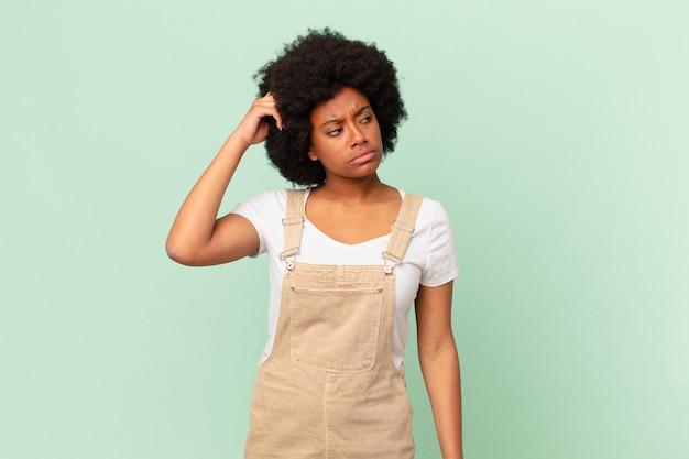 La donna afro si sente perplessa e confusa, si gratta la testa e guarda al concetto di chef laterale